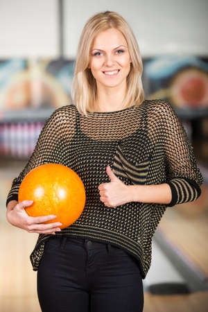 Beautiful young woman in a bowling alley is having fun. photo