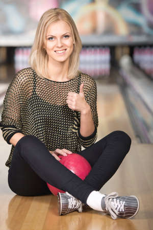 Beautiful smiling woman is sitting in a bowling alley. photo