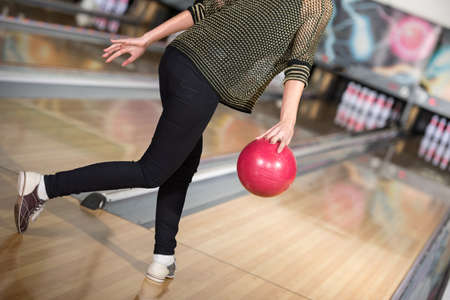 Young woman in club for bowling is throwing ball.