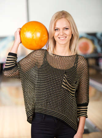 Woman in bowling alley. A woman is having fun while playing bowling. photo