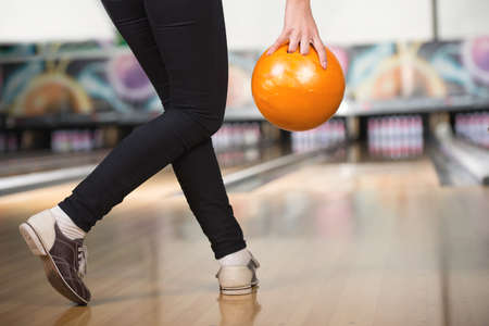 Young woman is playing bowling, preparing to throw ball. photo