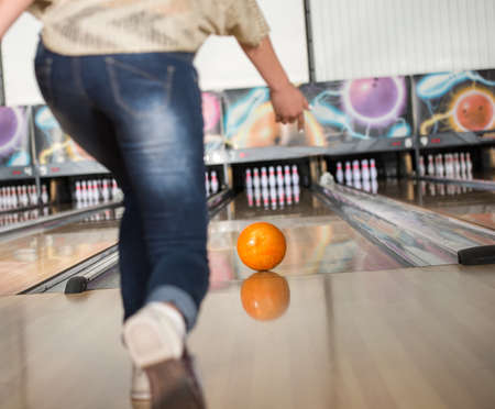 Young woman in club for bowling is throwing ball. photo