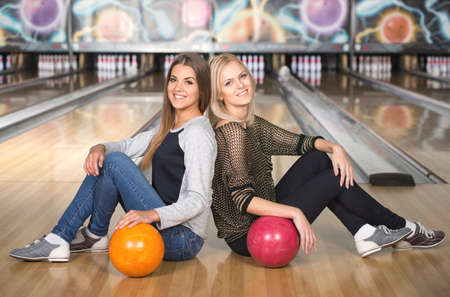 Cheerful young women are sitting in a bowling alley with balls. photo