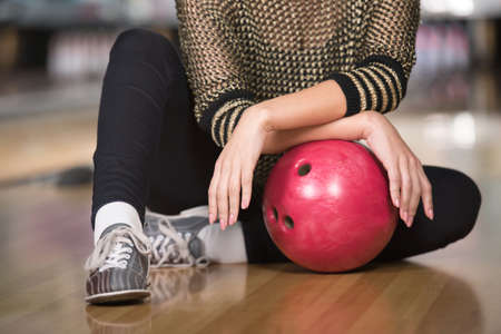 Portrait of woman is sitting in a bowling alley with bowling ball. photo