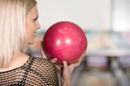 Portret van mooie jonge vrouw met een bowling bal in haar handen, achteraanzicht. Stockfoto