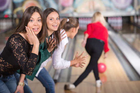 Girls in bowling looking into the camera, when their friend is throwing the ball.