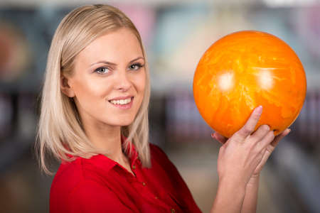 Beautiful young woman in a bowling alley with ball, is smiling and looking at the camera. photo
