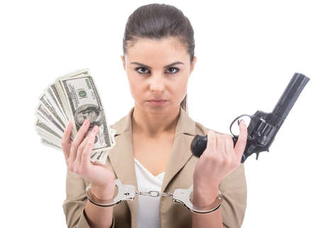 Young woman is holding in hand a lot american dollars and gun isolated on white background. A handcuffs on her hands. photo