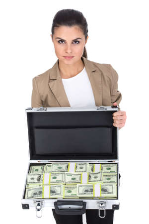 Beautiful young woman is holding a suitcase full of money, isolated on white background. photo