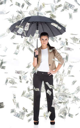 Young business woman with umbrella and money banknotes flying in air on the white background.