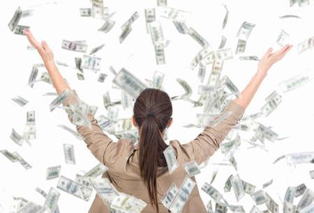 Jonge bedrijfsvrouw en geldbankbiljetten die in lucht op de witte achtergrond vliegen.