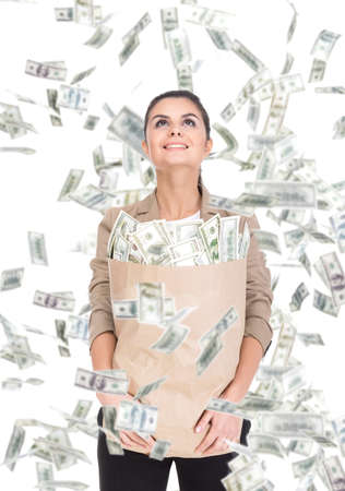 Young business woman with paper bags full of money and money banknotes flying in air on the white background. photo