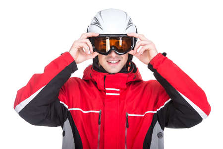 Portrait of young man in a ski suit and with ski goggles, isolated on white background. photo