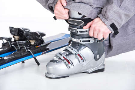 Close-up skis boots. Skier prepares for skiing. White background. photo