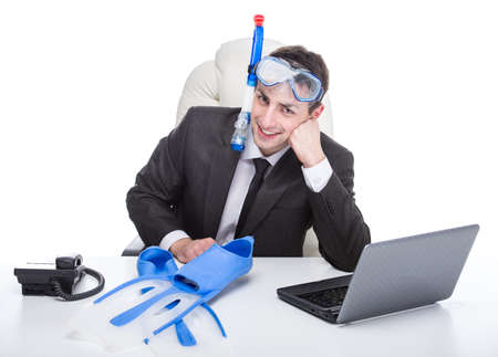 Young businessman in the office with diving equipment dreams about holiday. photo