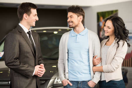 Handsome young car salesman is standing at the dealership telling about the features of the car to the customers. photo