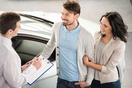 gente feliz: Vendedor de coches joven hermoso isnstanding en el concesionario diciendo acerca de las caracter�sticas del coche a la pareja. Foto de archivo
