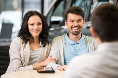 Some paperwork before buying a car. Young car salesman talking to a couple in auto salon. photo
