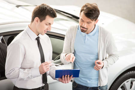 Car salesperson demonstrating a new automobile to young couple. Stock Photo