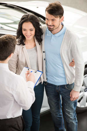 Handsome young car salesman isnstanding at the dealership telling about the features of the car to the couple. photo
