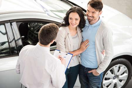 Beau jeune vendeur de voitures chez le concessionnaire isnstanding dire sur les caractéristiques de la voiture pour le couple.