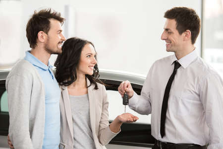 Car salesman is giving the key of the new car to the young attractive owners. photo
