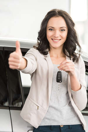 showroom: Happy young woman is holding keys to new car and looking at the camera.