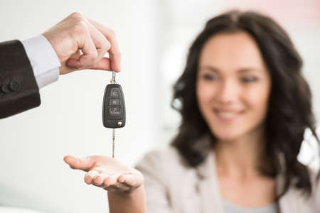 sales manager: Happy woman receives the keys to a new car from a sales manager.