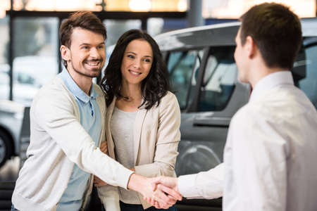 sales manager: Young couple grateful sales manager for advice in auto salon.