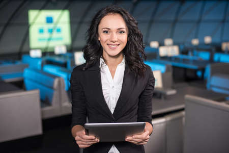 Portrait of a smiling young woman with tablet is standing in the background of the modern conference hall. Stock Photo