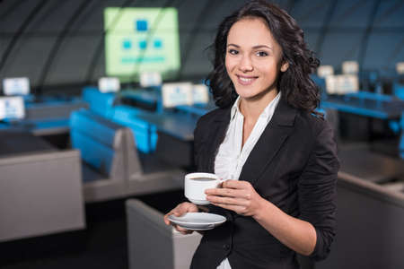 spokesman: Portrait of a smiling young woman is drinking a coffee in the background of the modern conference hall. Stock Photo