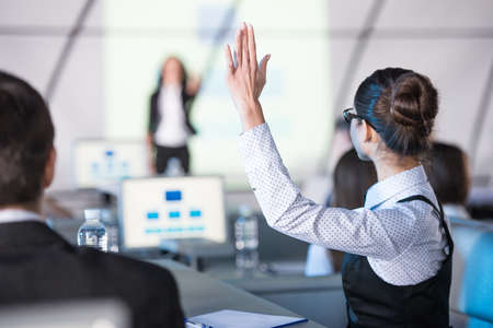 large group of business people: Rear view of young woman raised her hand during presentation.