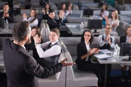 personas escuchando: Vista trasera del altavoz masculina en el podio.
