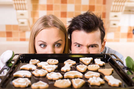 kiss biscuits: Young beautiful couple pulled the cookies from the oven. Stock Photo