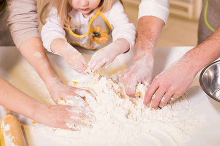 Close-up hands of family are baking cakes in home kitchen.