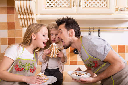 Portrait of beautiful, funny family with pastries. photo