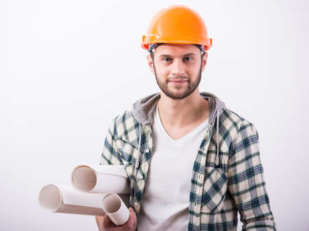 Young male engineer with helmet is holding blueprints, on grey background. photo