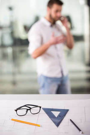 architect tools: Portrait of architect is working with blueprint in the office. Focus on table with tools. Stock Photo