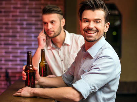 beer after work: Two young handsome friends in a pub with bottle of beer are spending time together.
