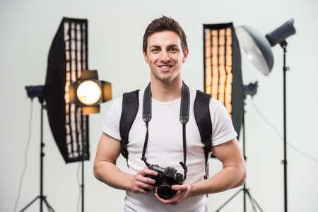 Jonge glimlachende fotograaf met camera in de professioneel ingerichte studio.