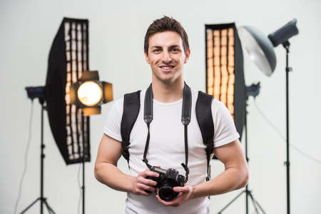 Young smiling photographer with camera in professionally equipped studio. Фото со стока
