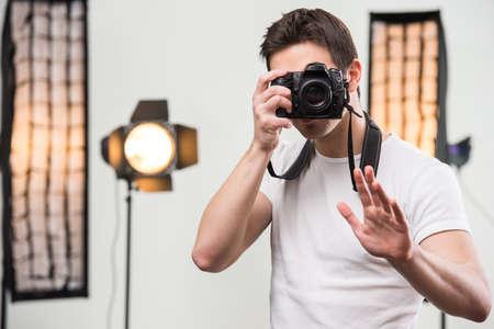 전문적으로 장착 된 스튜디오에서 카메라와 함께 젊은 웃는 사진 작가.
