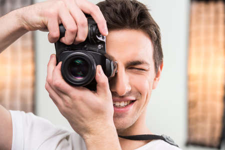 professionally: Young smiling photographer with camera in professionally equipped studio. Close-up.