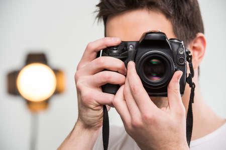 při pohledu na fotoaparát: Usměvavá fotograf s kamerou v profesionálně vybaveném studiu. Close-up. Reklamní fotografie
