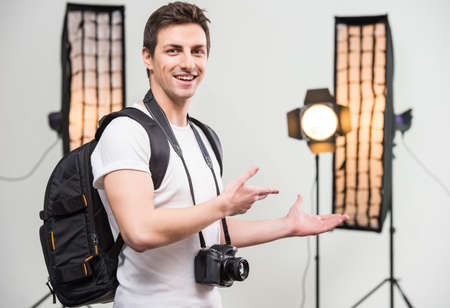lens unit: Young smiling photographer with camera in professionally equipped studio. Close-up.