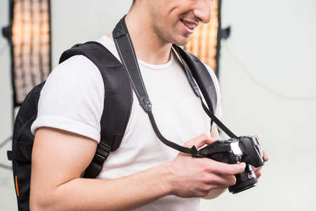 lens unit: Young photographer with camera in professionally equipped studio is looking at the camera.
