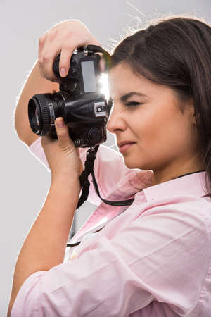 professionally: Young female photographer with camera in professionally equipped studio.