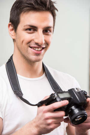 lens unit: Young smiling photographer with camera on the gray background. Close-up.