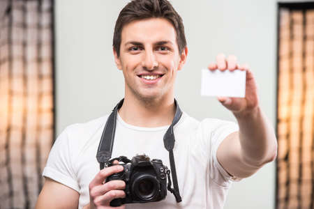 lens unit: Young smiling photographer with camera is showing visit card in professionally equipped studio.