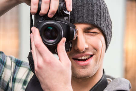 professionally: Young smiling photographer with camera in professionally equipped studio. Stock Photo